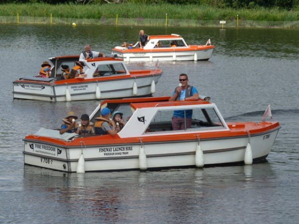 When considering UK staycation ideas, a day boat is a popular day activity for many visitors. Photograph shows 3 orange and white day boats with passengers on board eating whippy ice cream cones.