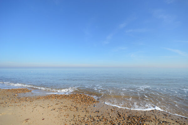 An image to inspire UK Staycation Ideas, showing Hemsby's beach. The picture shows a big, blue sky and horizon and a sandy-stony beach with white wash.